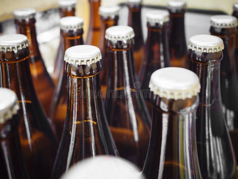 Cervejarias da cerveja que empacotam garrafas com fim do tampão acima imagem de stock