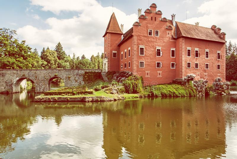 Cervena Lhota is a beautiful chateau in Czech republic. It stands at the middle of a lake on a rocky island. Travel destination. Mirrored architecture. Yellow stock image