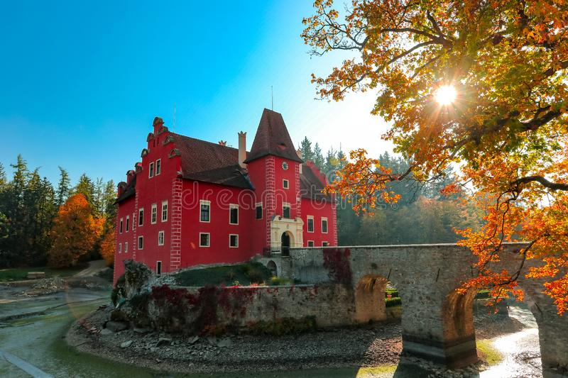 Cervena Lhota Castle in Czech Republic. Beautiful small red chateau Cervena Lhota, Castle in Czech Republic in autumn season with fall color and drained pond stock photography