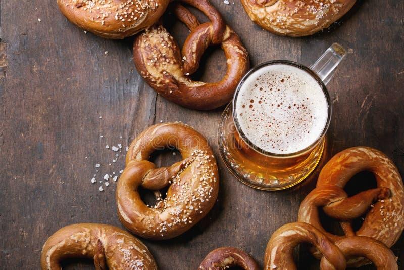 Cerveza de cerveza dorada con los pretzeles imágenes de archivo libres de regalías