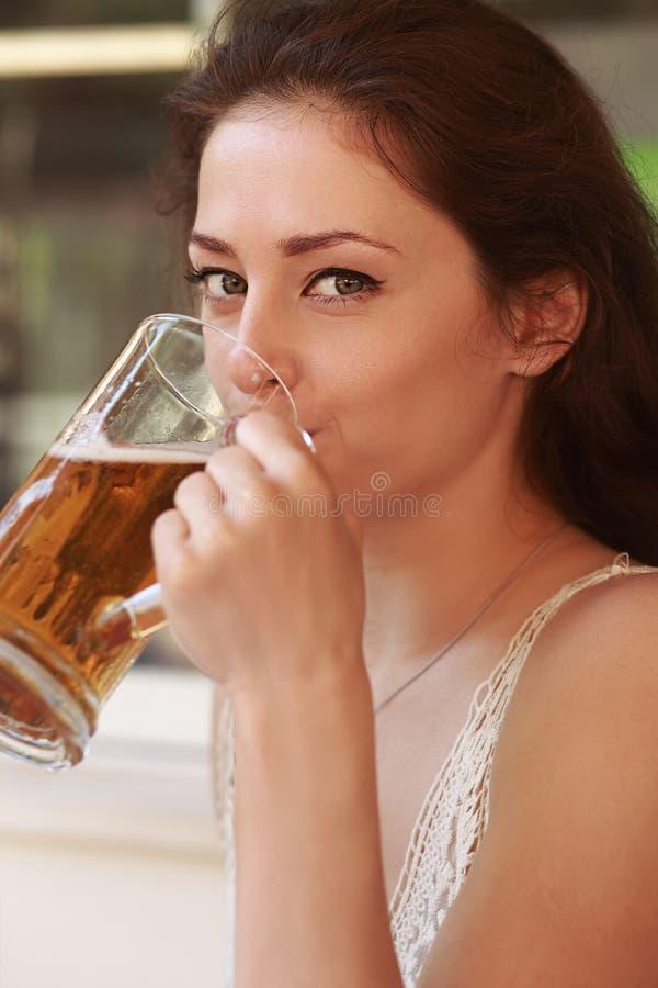 Cerveza de cerveza dorada de consumición de la mujer hermosa primer imagen de archivo libre de regalías