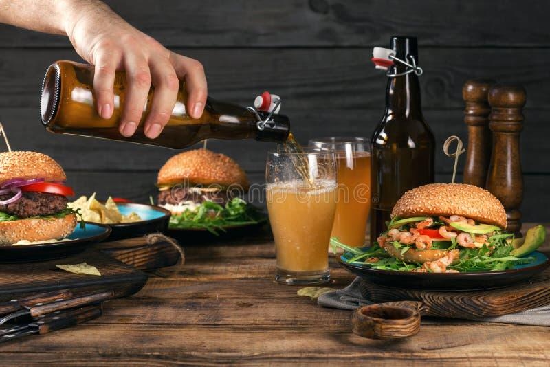Cerveza de cerveza dorada en la tabla de madera con una variedad de hamburguesas imagen de archivo