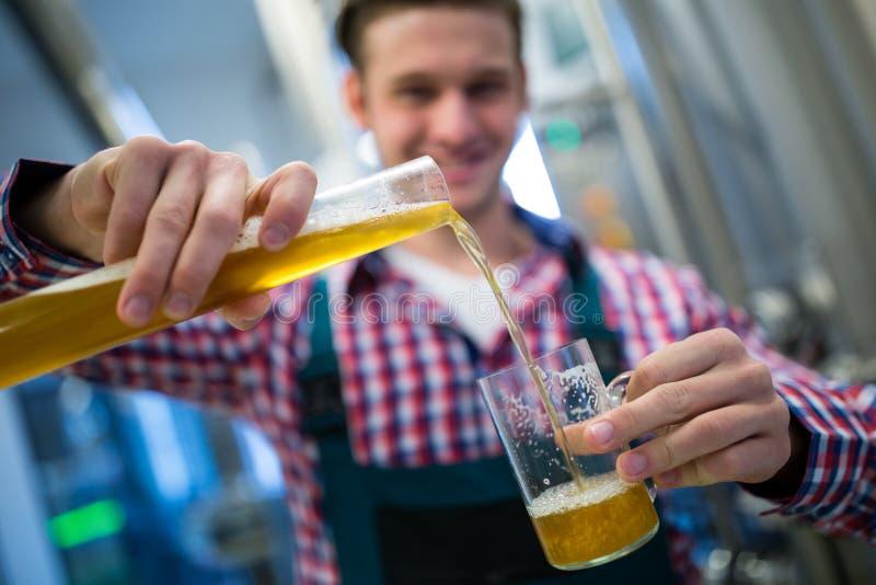 Cerveza de colada del cervecero en vidrio foto de archivo libre de regalías