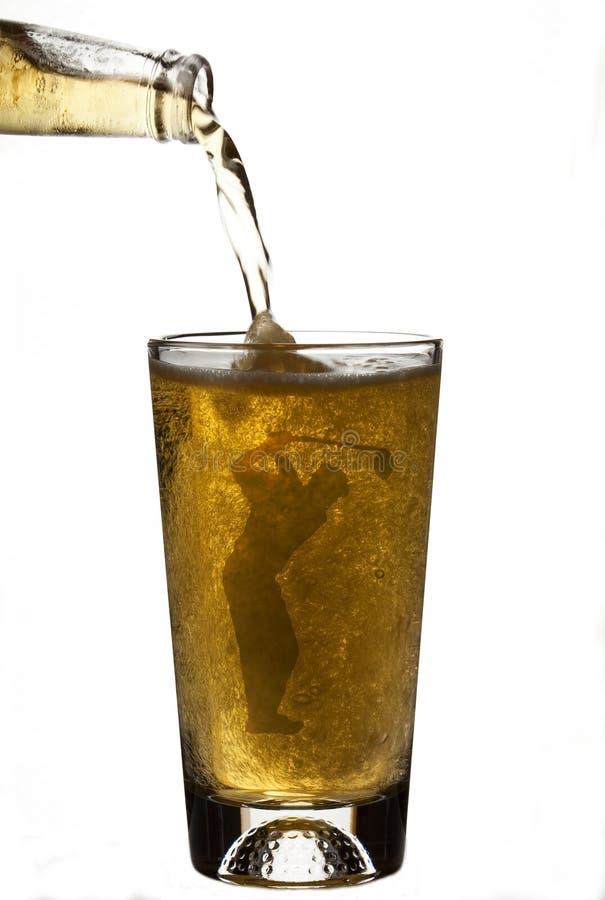 Cerveza de colada en el vidrio de cerveza del golfista imágenes de archivo libres de regalías