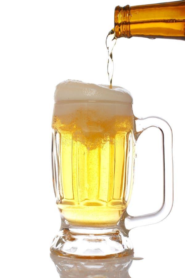 Cerveza de colada en la taza fotografía de archivo libre de regalías