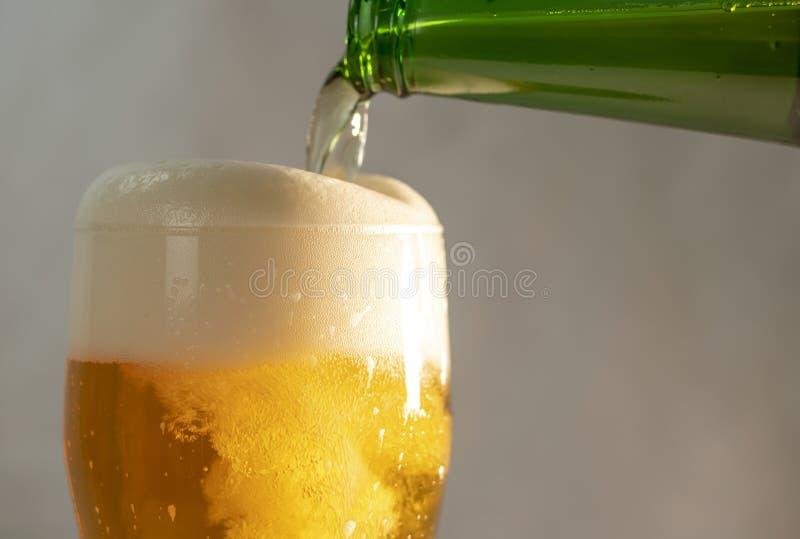 Cerveza de colada en un vidrio de una botella foto de archivo libre de regalías