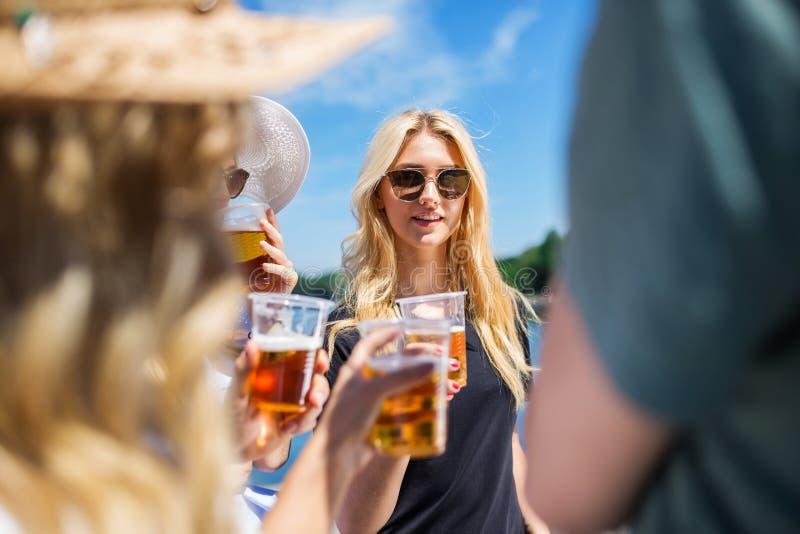 Cerveza de consumición de la mujer con sus amigos fotos de archivo