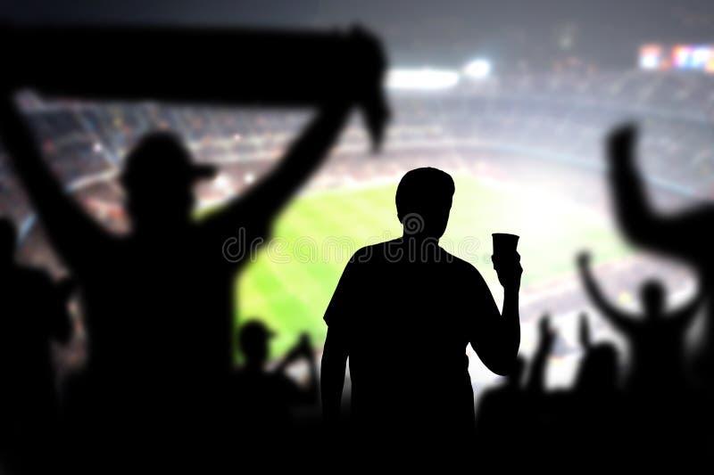 Cerveza de consumición del fanático del fútbol en muchedumbre en estadio imagen de archivo