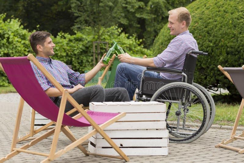 Cerveza de consumición del hombre discapacitado con el amigo fotografía de archivo libre de regalías