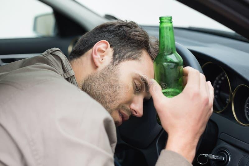 Cerveza de consumición del hombre mientras que conduce foto de archivo