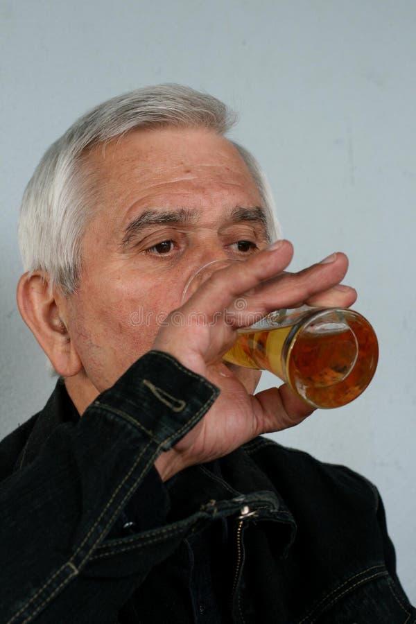 Cerveza de consumición del pensionista fotografía de archivo libre de regalías