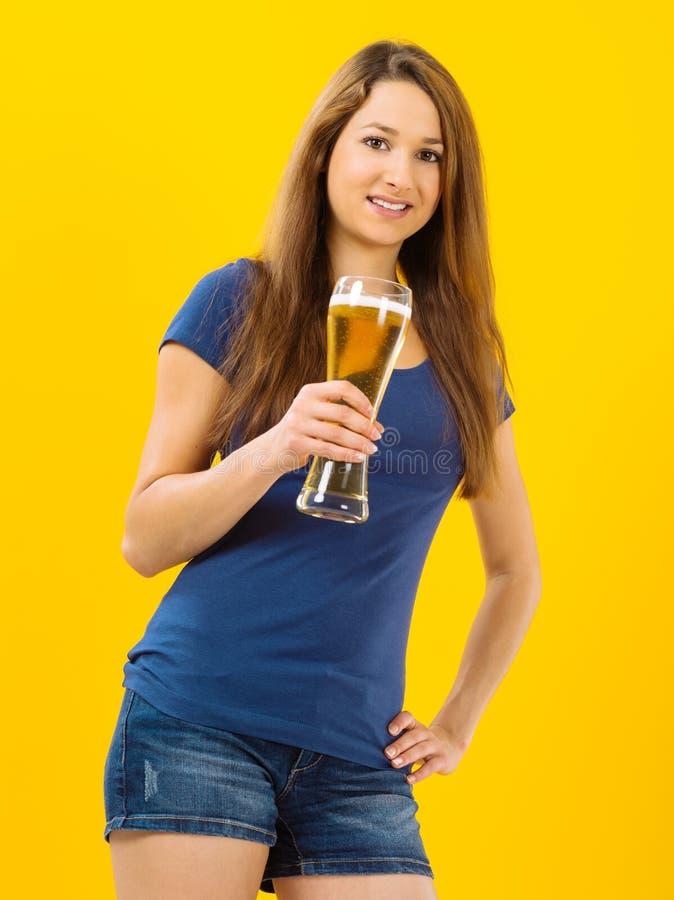 Cerveza de consumición sonriente de la mujer joven fotos de archivo libres de regalías