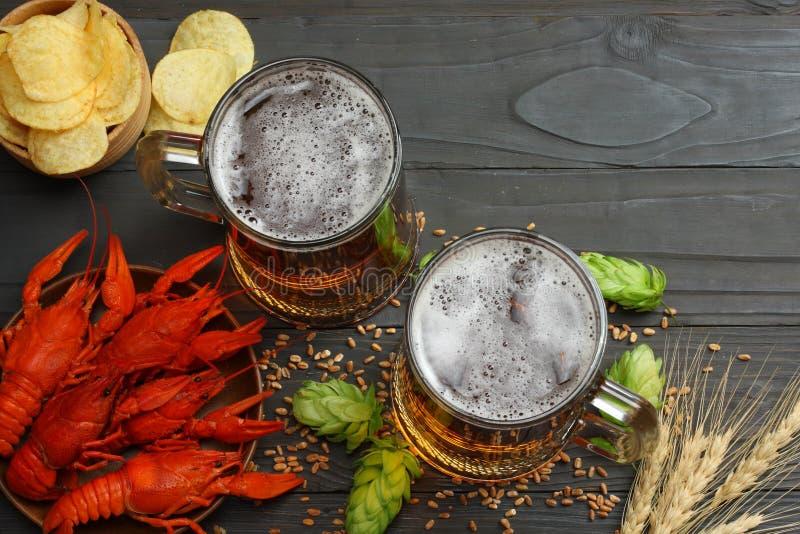 Cerveza de cristal con los cangrejos, los conos de salto y los oídos del trigo en fondo de madera oscuro Concepto de la cervecerí imagen de archivo