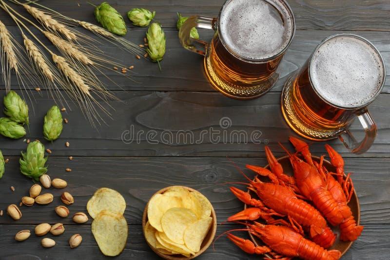 Cerveza de cristal con los cangrejos, los conos de salto y los oídos del trigo en fondo de madera oscuro Concepto de la cervecerí imagenes de archivo