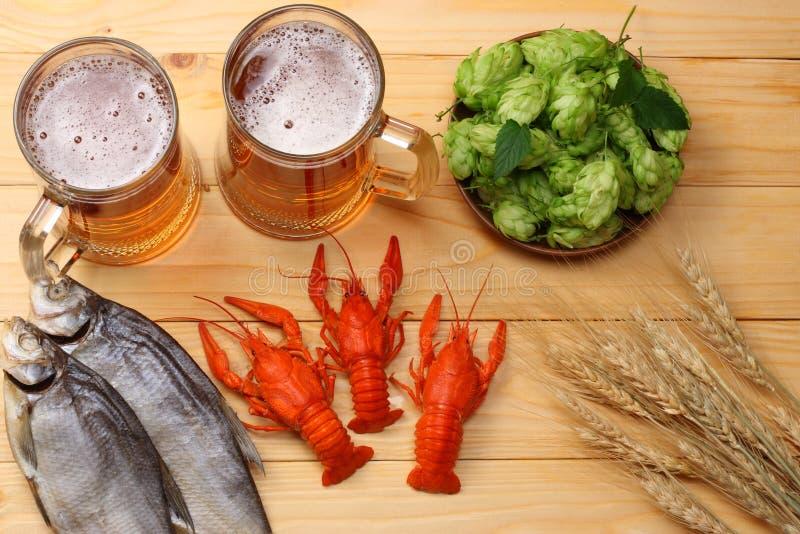 Cerveza de cristal con los cangrejos, los pescados secados y los conos de salto en fondo de madera ligero Concepto de la cervecer fotografía de archivo libre de regalías