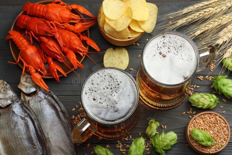 Cerveza de cristal con los cangrejos, los pescados secados y los conos de salto en fondo de madera oscuro Concepto de la cervecer foto de archivo libre de regalías