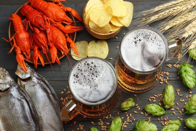 Cerveza de cristal con los cangrejos, los pescados secados y los conos de salto en fondo de madera oscuro Concepto de la cervecer imagen de archivo libre de regalías