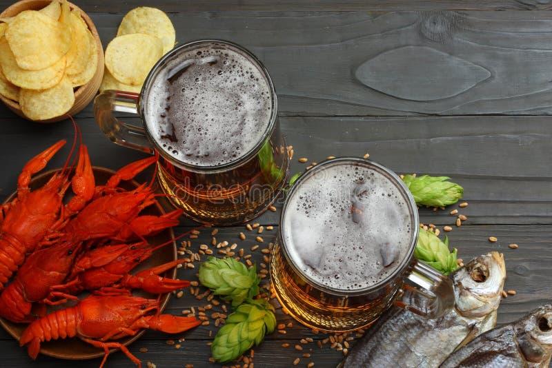 Cerveza de cristal con los cangrejos, los pescados secados y los oídos del trigo en fondo de madera oscuro Concepto de la cervece fotografía de archivo libre de regalías