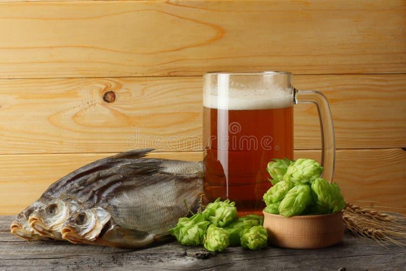 Cerveza de cristal con los conos de salto, los pescados secados y los oídos del trigo en fondo de madera ligero Concepto de la ce fotografía de archivo