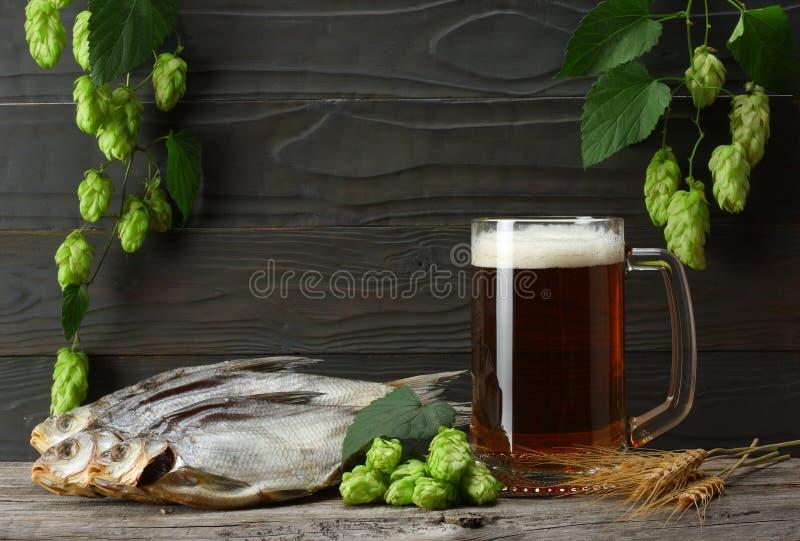 Cerveza de cristal con los conos de salto, los pescados secados y los oídos del trigo en fondo de madera oscuro Concepto de la ce imagen de archivo libre de regalías