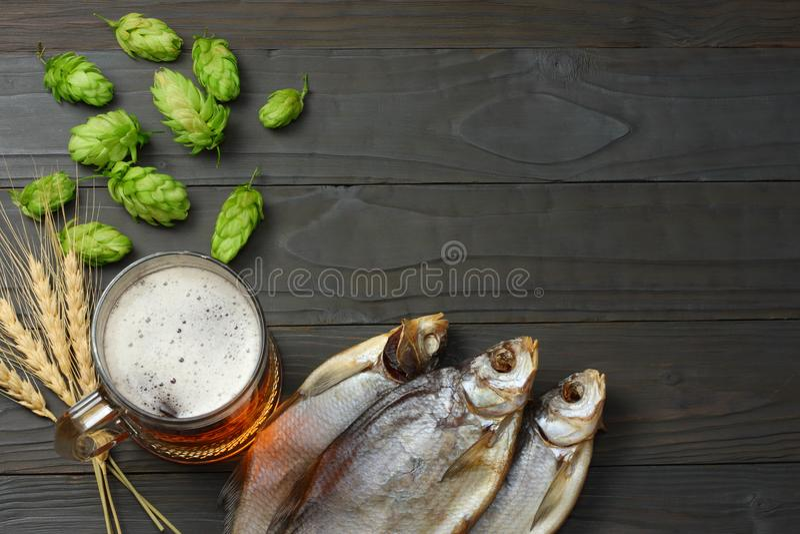 Cerveza de cristal con los conos de salto, los pescados secados y los oídos del trigo en fondo de madera oscuro Concepto de la ce fotos de archivo libres de regalías