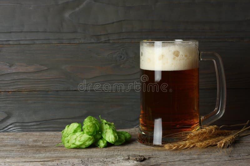 Cerveza de cristal con los conos de salto y los oídos del trigo en fondo de madera oscuro con el espacio de la copia Concepto de  imagen de archivo libre de regalías