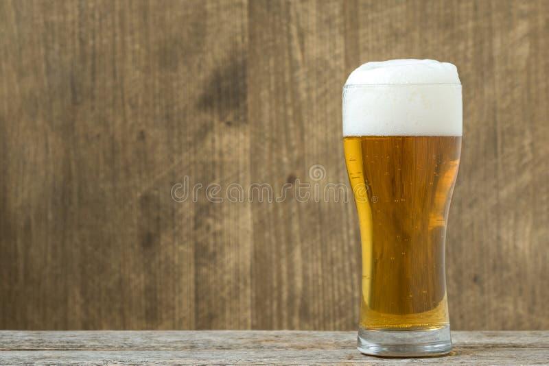 Cerveza de cristal en el fondo de madera fotos de archivo
