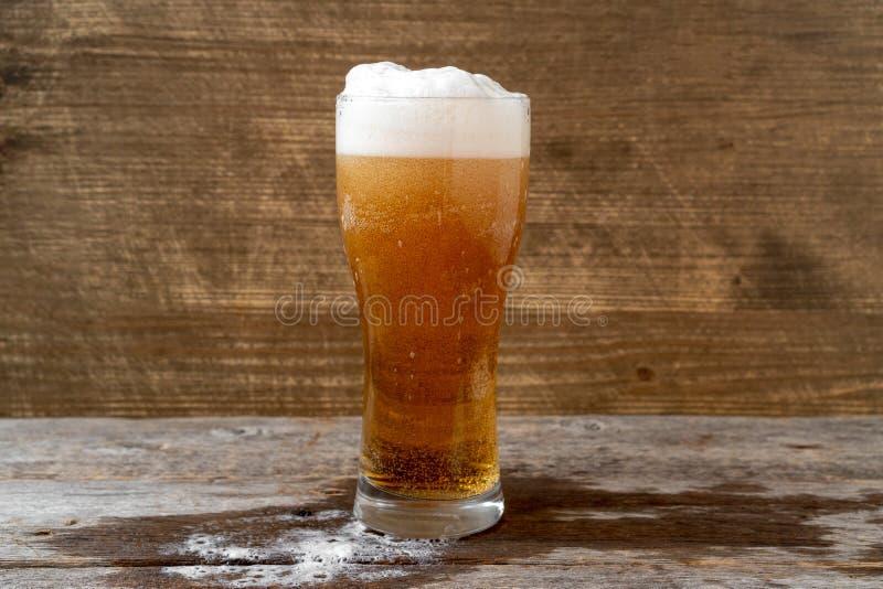 Cerveza de cerveza dorada con la espuma blanca foto de archivo libre de regalías