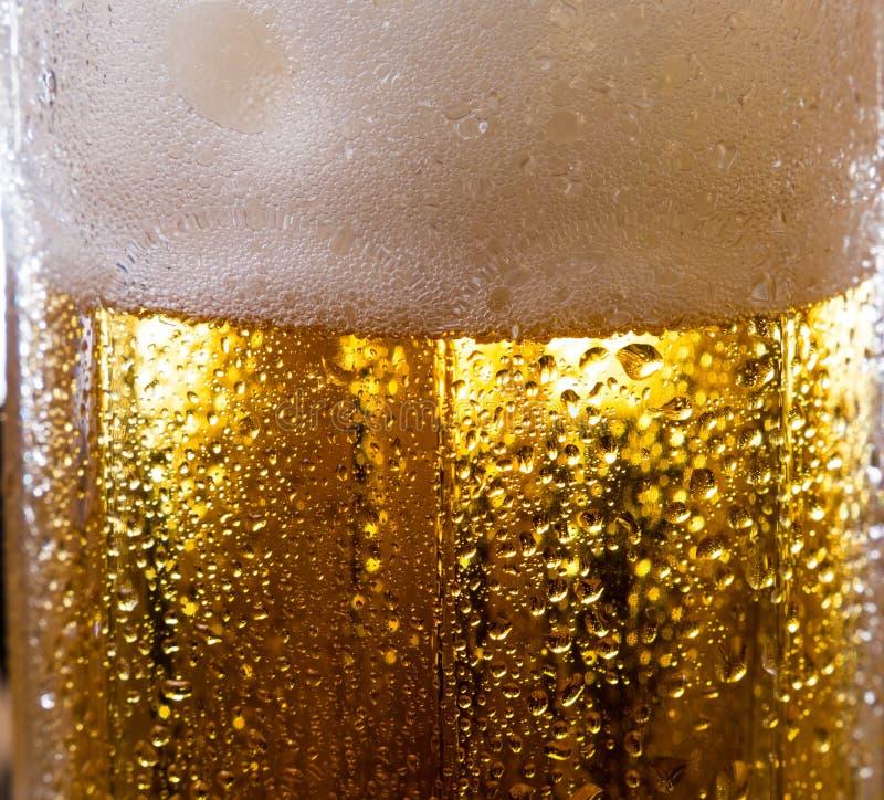 Cerveza de la bebida del alcohol en imagen macra con las chispas y la espuma foto de archivo