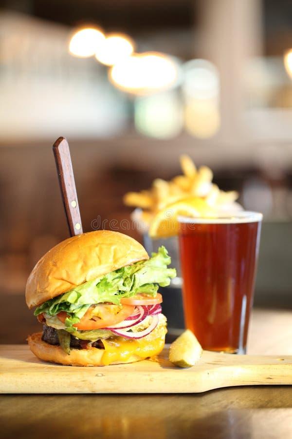 Cerveza del arte con la hamburguesa deliciosa foto de archivo