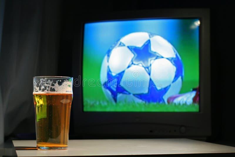 Cerveza dorada y balompié en la TV foto de archivo libre de regalías