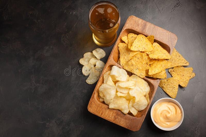 Cerveza en primer de los vidrios en la tabla concreta La cerveza y los bocados son microprocesadores y nachos en cuenco de madera imagenes de archivo