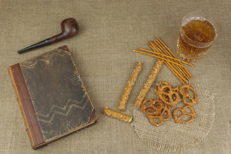 Cerveza en un vidrio y un libro en la tabla Paja curruscante del trigo con la sal Pila de palillos del pretzel fotos de archivo