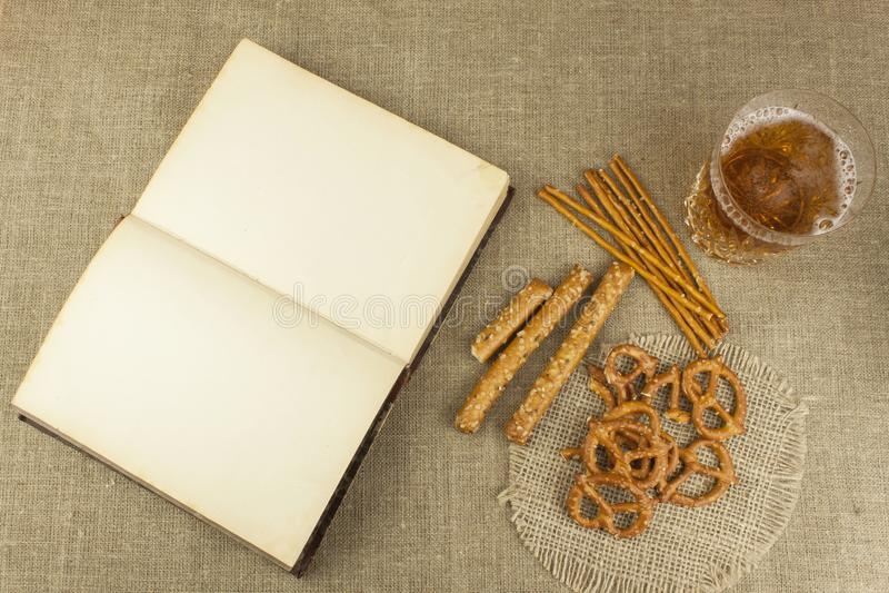 Cerveza en un vidrio y un libro en la tabla Paja curruscante del trigo con la sal Pila de palillos del pretzel imágenes de archivo libres de regalías