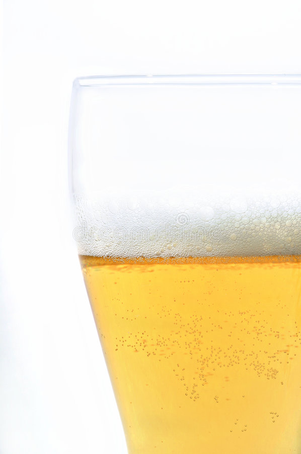 Cerveza en vidrio con la espuma aislada en blanco foto de archivo