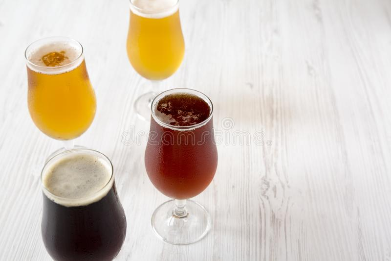 Cerveza fría clasificada en un fondo de madera blanco, vista lateral del arte Copie el espacio fotos de archivo libres de regalías