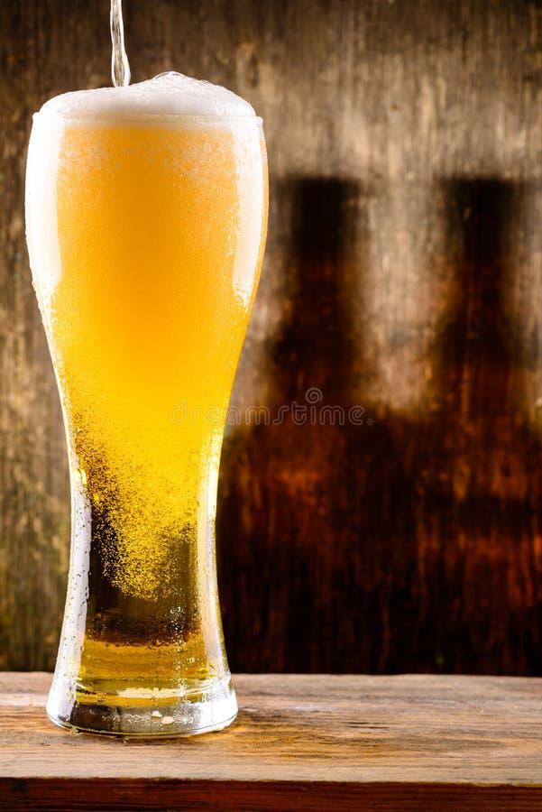 Cerveza ligera fría fresca que vierte en el vidrio con descensos del agua encendido imágenes de archivo libres de regalías