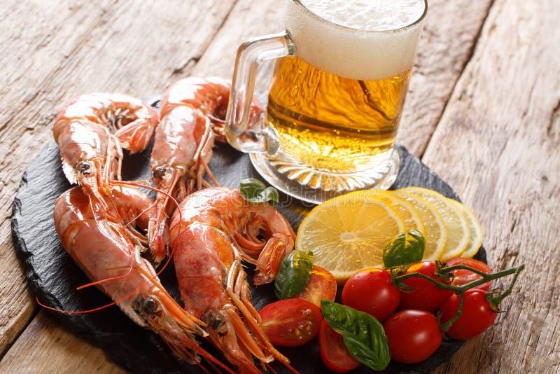 Cerveza ligera tradicional y camarones, limón y primer sabrosos de los tomates en un tablero de la pizarra horizontal fotografía de archivo