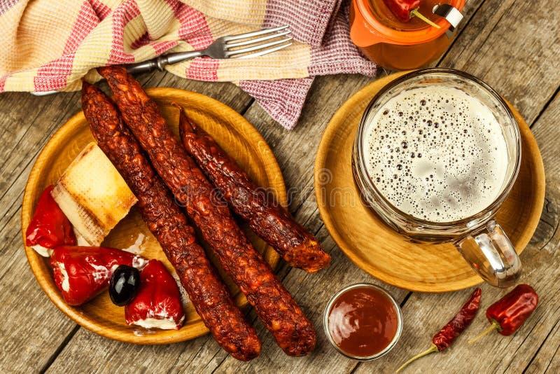 Cerveza oscura en salchichas de cristal y picantes con pimientas de chile Salchichas secadas en la tabla imágenes de archivo libres de regalías