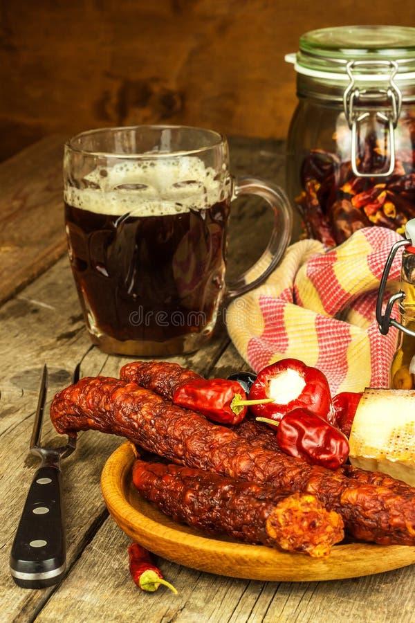 Cerveza oscura en salchichas de cristal y picantes con pimientas de chile Salchichas secadas en la tabla fotografía de archivo libre de regalías