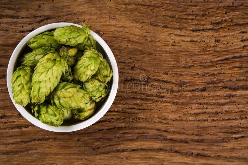 Cerveza que elabora los conos de salto de los ingredientes en el cuenco blanco en fondo de madera Concepto de la cervecería de la fotos de archivo libres de regalías