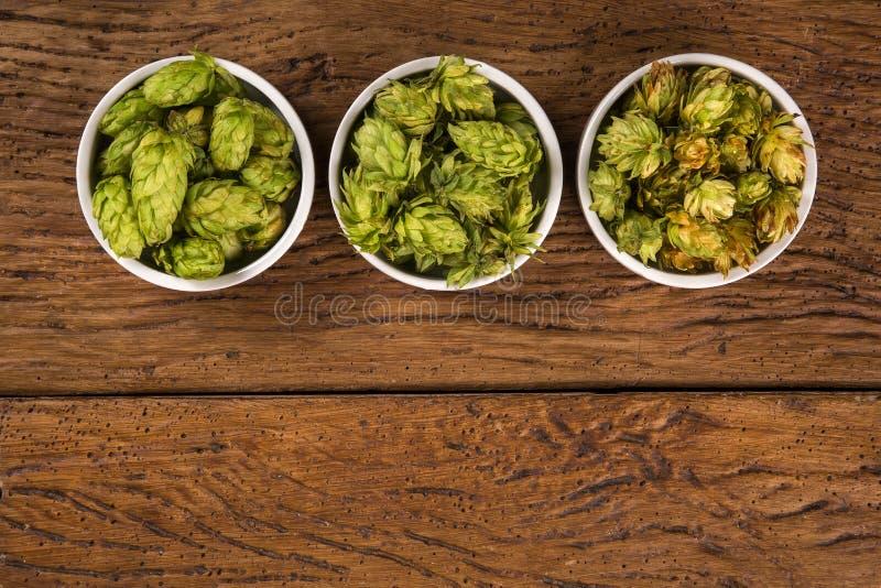 Cerveza que elabora los conos de salto de los ingredientes en el cuenco blanco en fondo de madera Concepto de la cervecería de la imagen de archivo