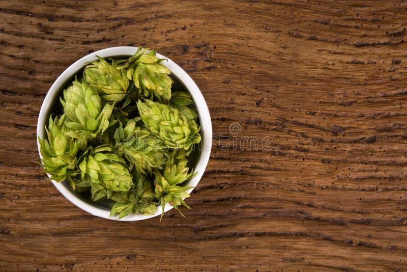 Cerveza que elabora los conos de salto de los ingredientes en oídos de madera del cuenco y del trigo en fondo de madera Concepto  imagenes de archivo