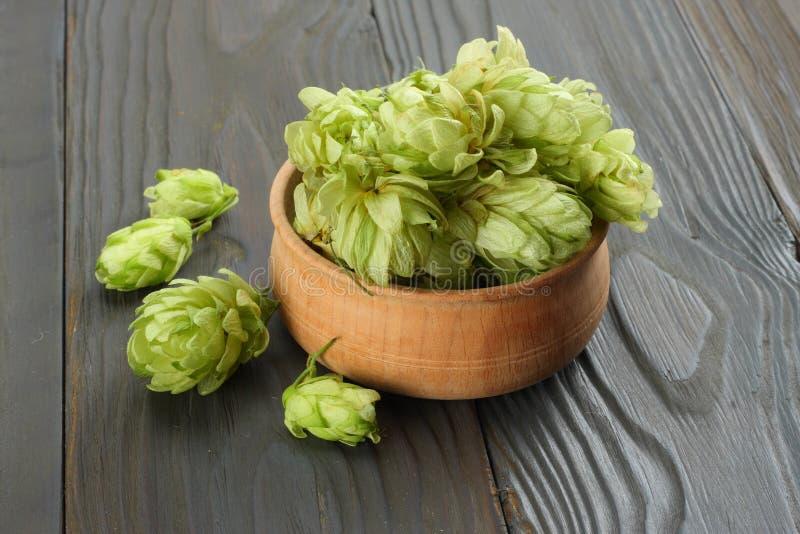 Cerveza que elabora los conos de salto de los ingredientes en oídos de madera del cuenco y del trigo en fondo de madera oscuro Co imagenes de archivo
