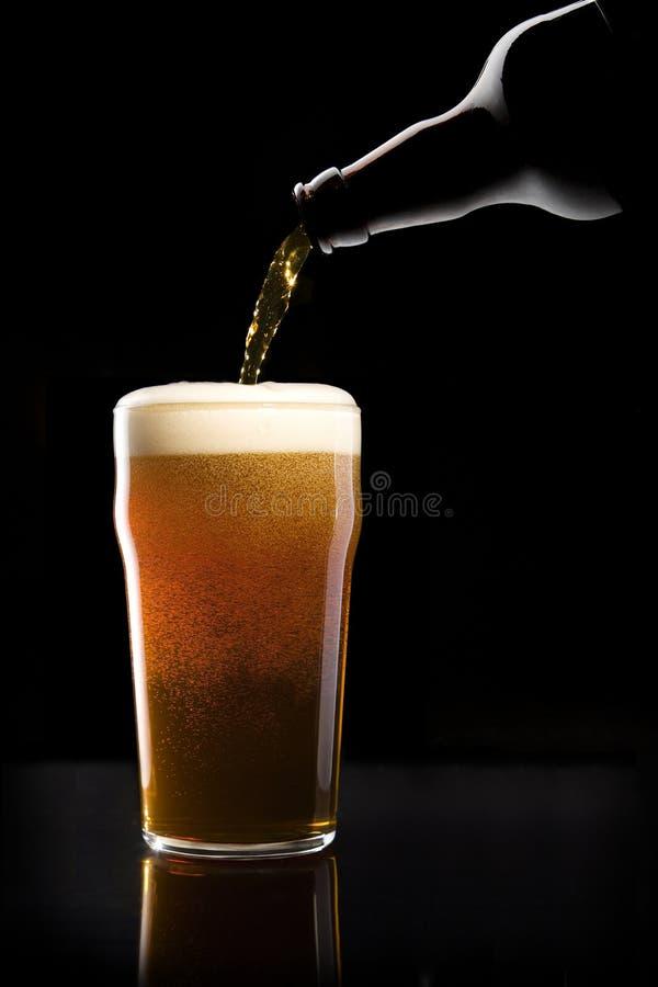 Cerveza que es vertida en el vidrio fotos de archivo libres de regalías
