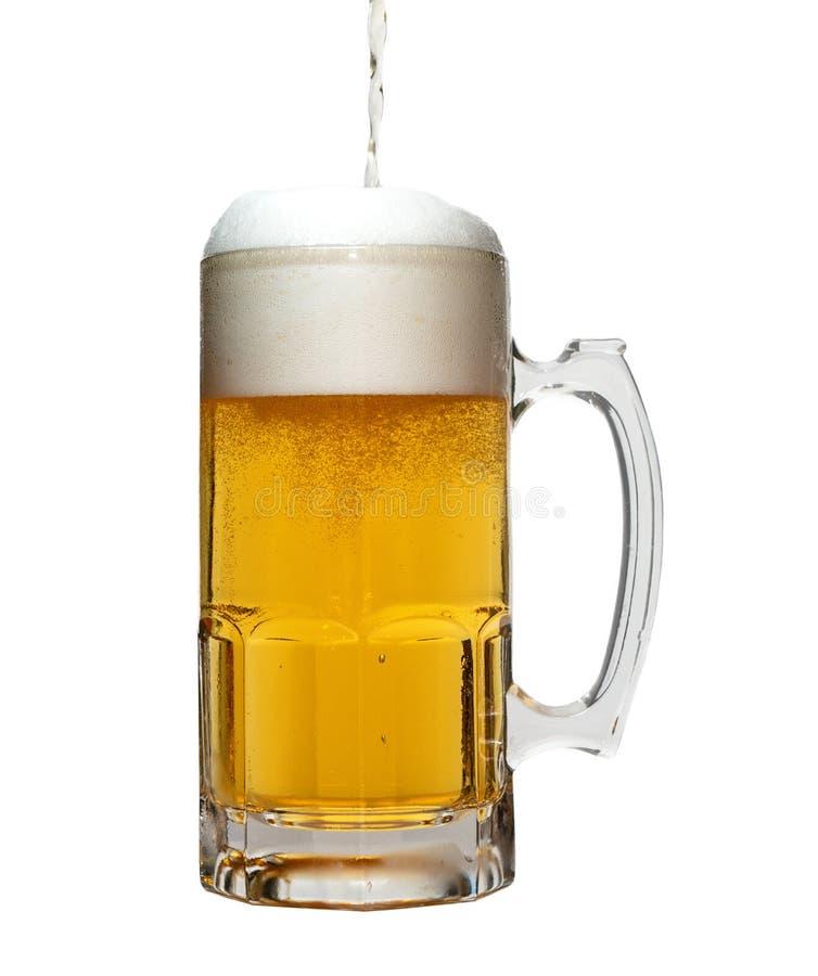 Cerveza que es vertida en la taza foto de archivo