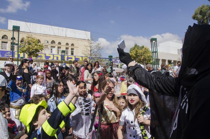 Cerveza-Sheva, ISRAEL - 5 de marzo de 2015: Los niños en trajes del carnaval cogen los regalos en el banquete de Purim fotos de archivo libres de regalías