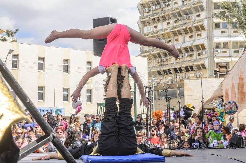 Cerveza-Sheva, ISRAEL - 5 de marzo de 2015: Muchacha-acróbata en la posición de la cabeza-abajo - Purim imagen de archivo libre de regalías