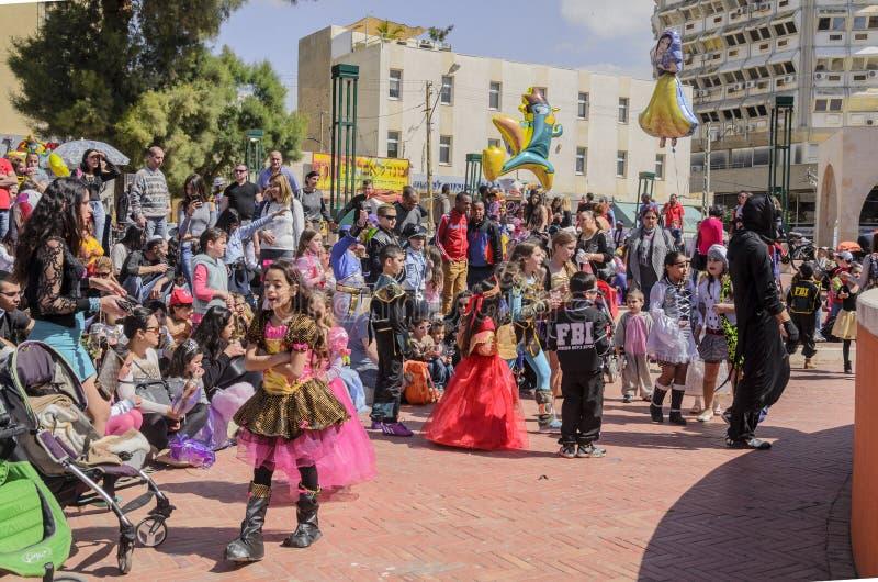 Cerveza-Sheva, ISRAEL - 5 de marzo de 2015: Niños en trajes del carnaval con sus padres en la calle en conmemoración de Purim foto de archivo libre de regalías