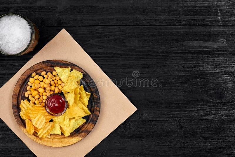 Cerveza y bocados de cerveza dorada en la tabla de madera negra Nueces, microprocesadores Visión superior con Copyspace fotos de archivo